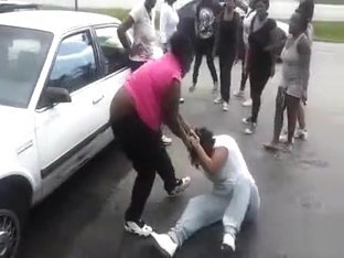 Angry black women fight in a parking lot